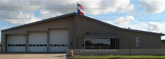 Tan building with 3 large garage doors and a flag pole - La Porte EMS Headquarters